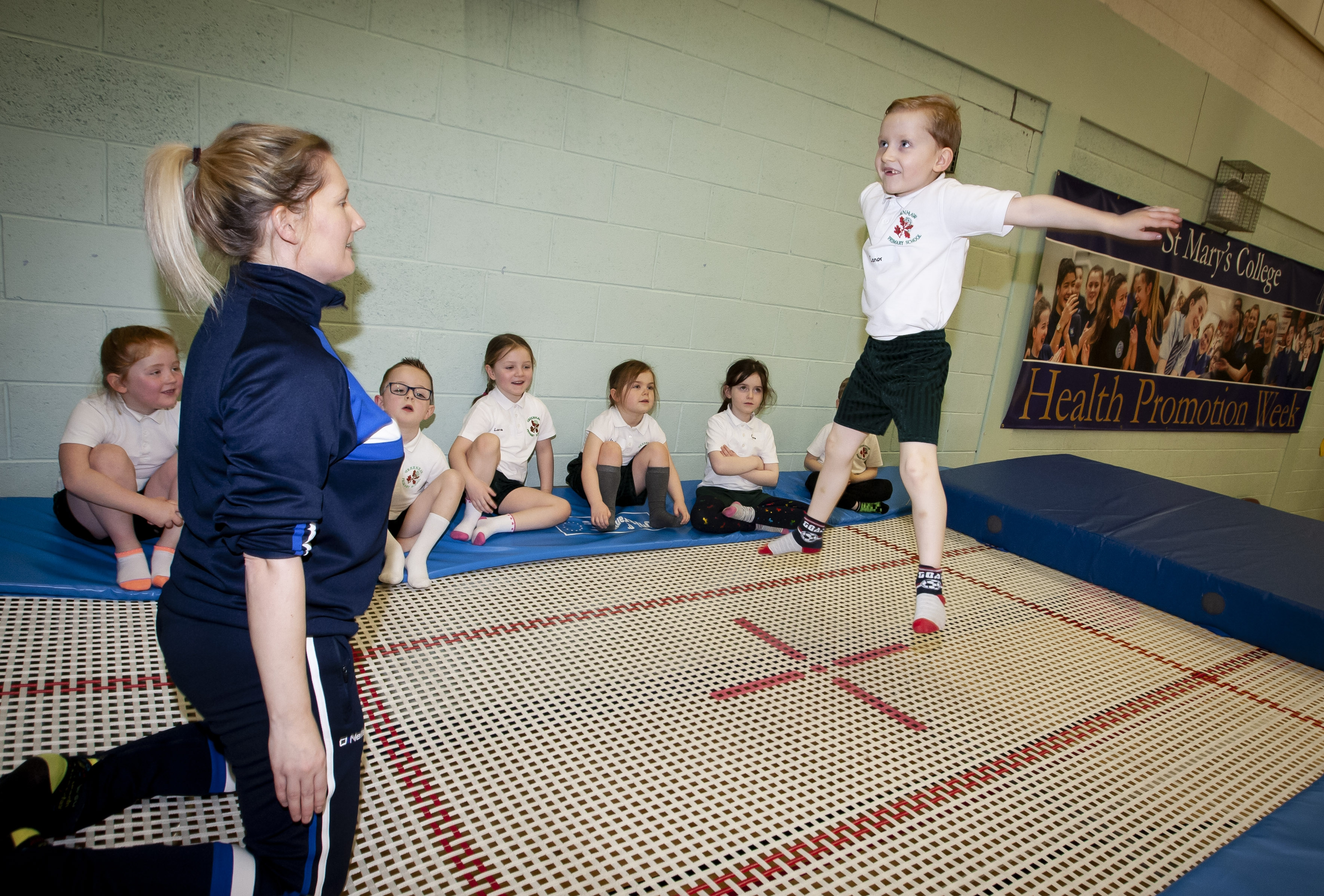 Head of PE at St. Mary's College, Mrs. Jennifer Martin pictured putting her son Conor, a P2 pupil from Greenhaw PS through his paces on the trampoline during Health Promotion Week at the college on Friday morning. (Photos: Jim McCafferty Photography)